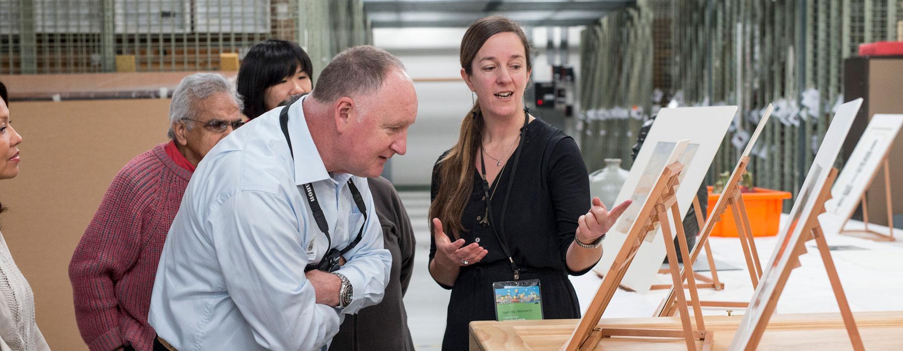 Curator showing visitors artwork