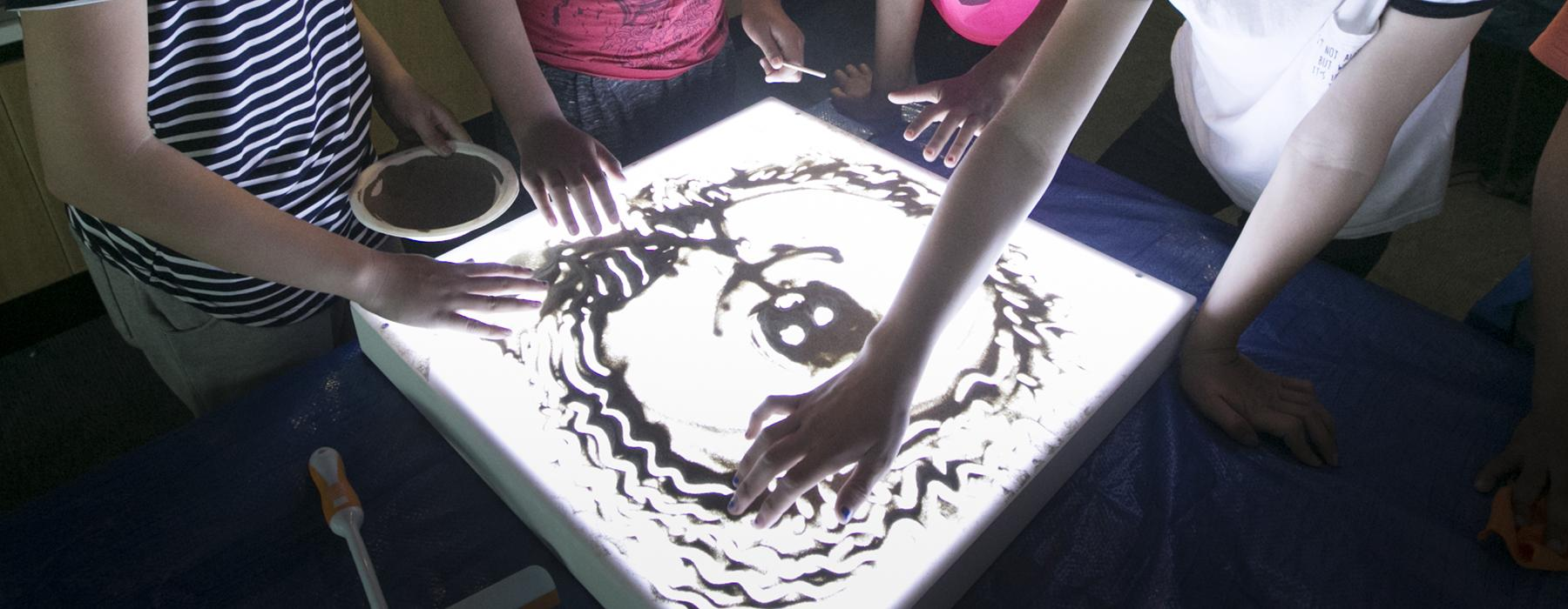 Children drawing on a sandbox (a light box with sand on top of it)