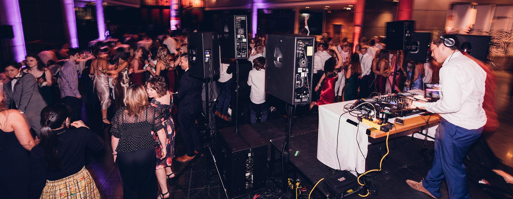Young adults dancing in front of a DJ booth