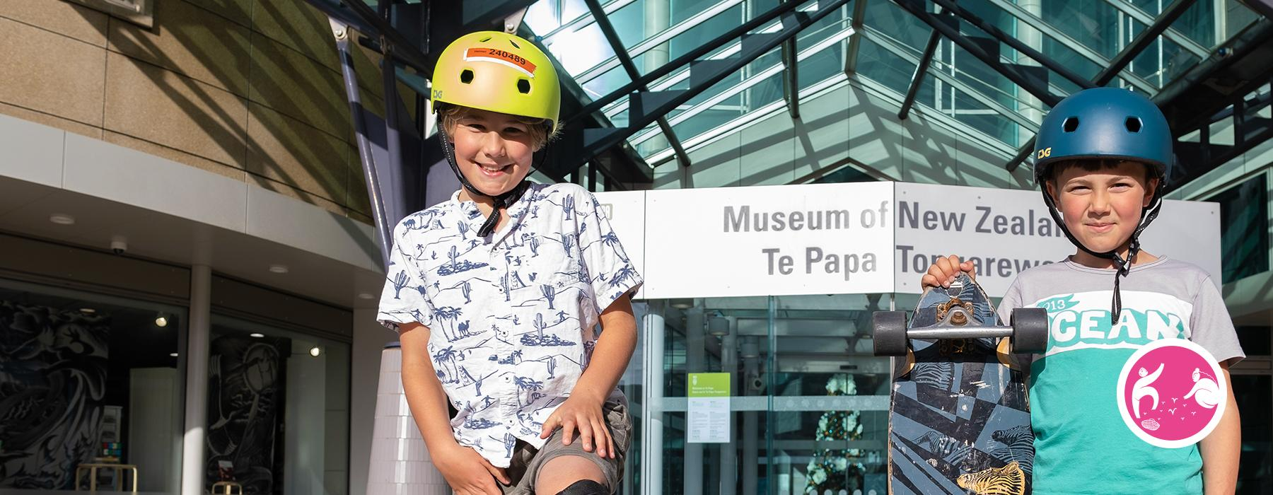 Two young boys pose outside Te Papa with their skateboards