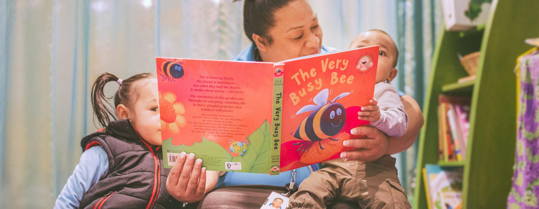 A woman reads a book to two children