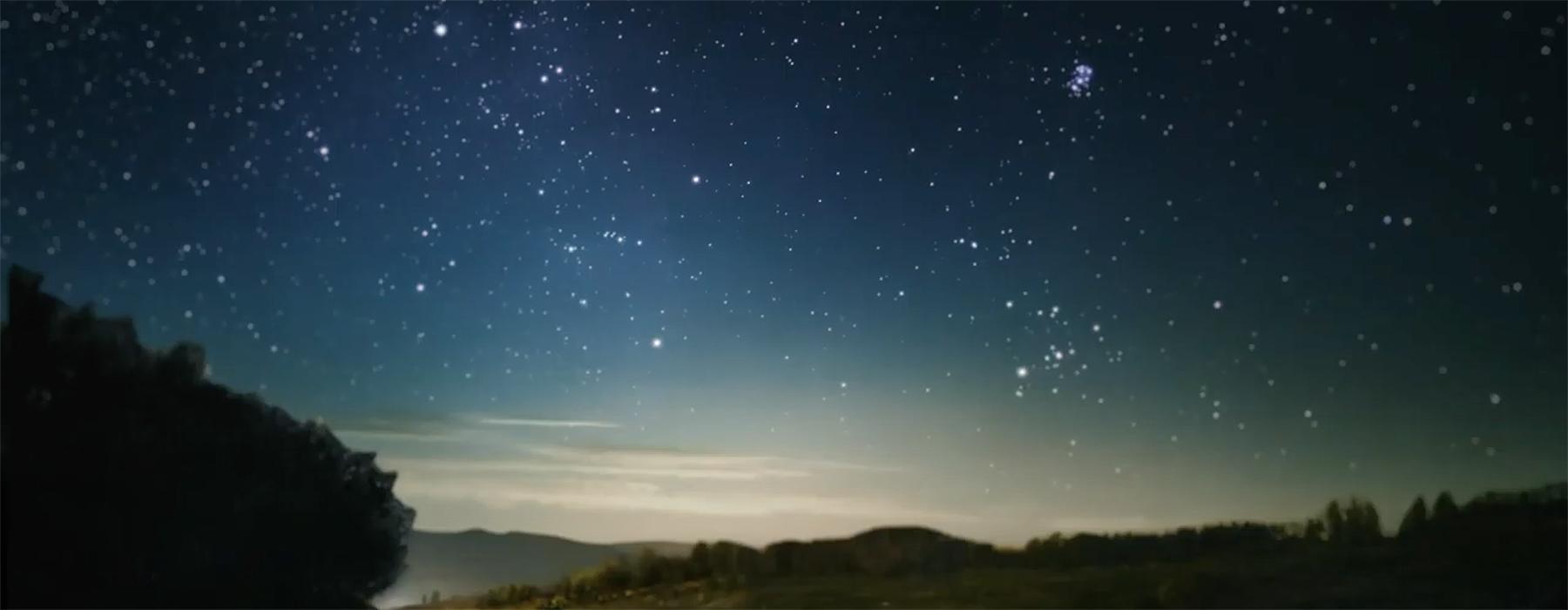 A starry sky over a darkened landscape