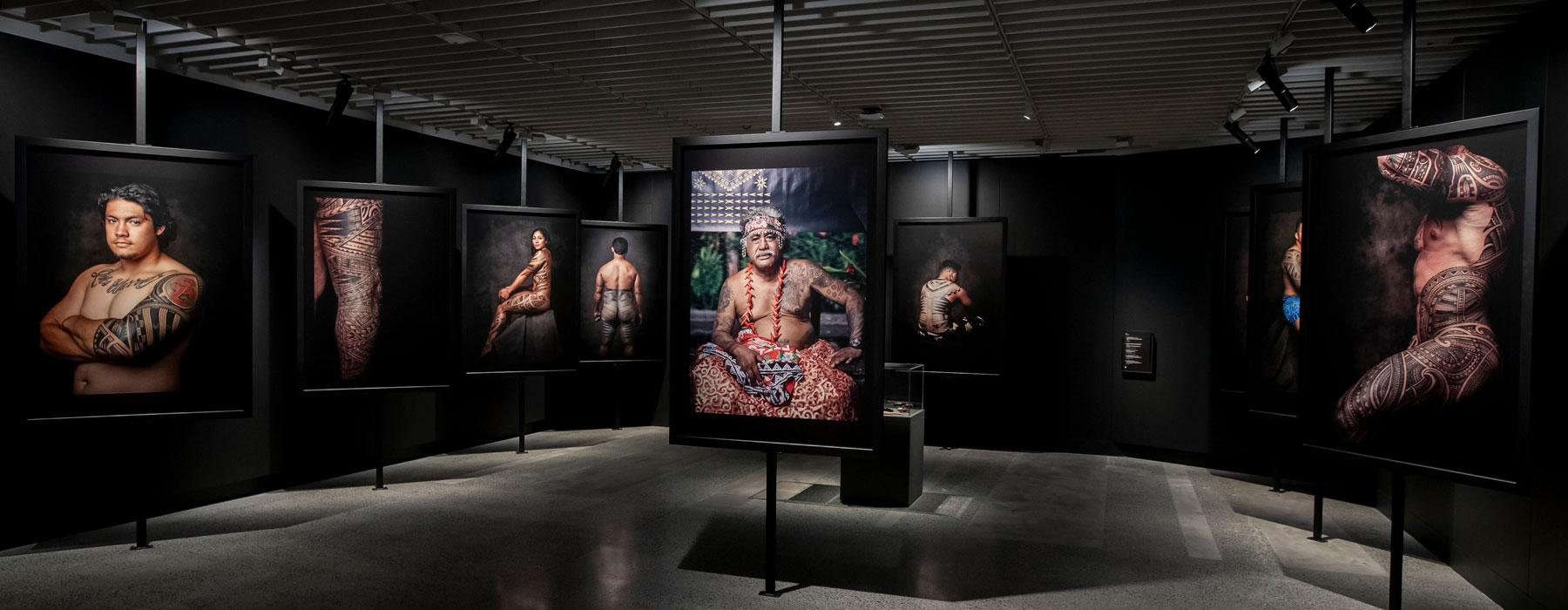 Inside an exhibition, large photographs of tattooed men and women hang on the walls