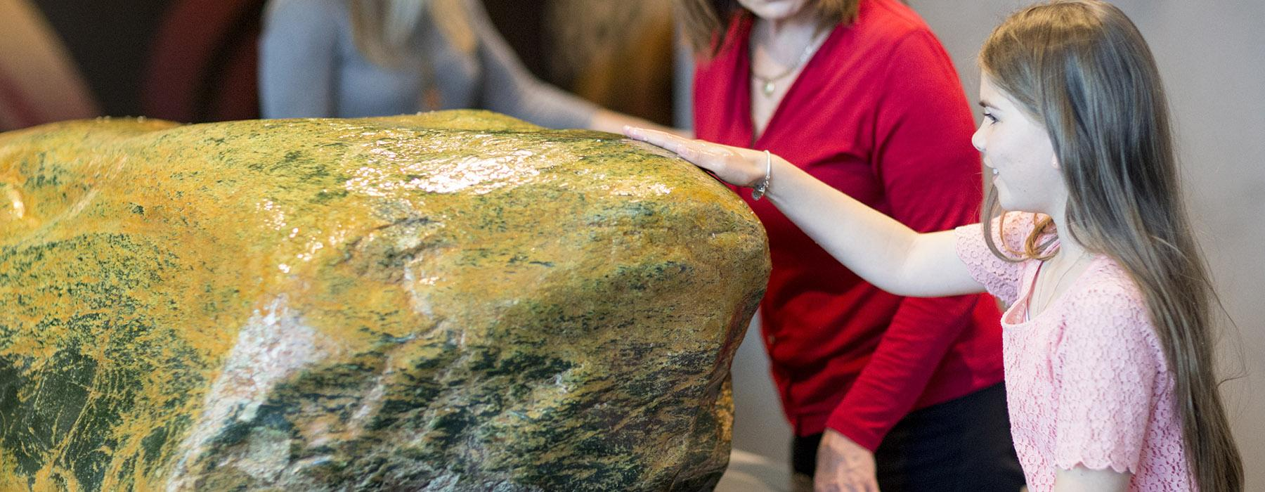 A little girl touches the greenstone in Te Marae