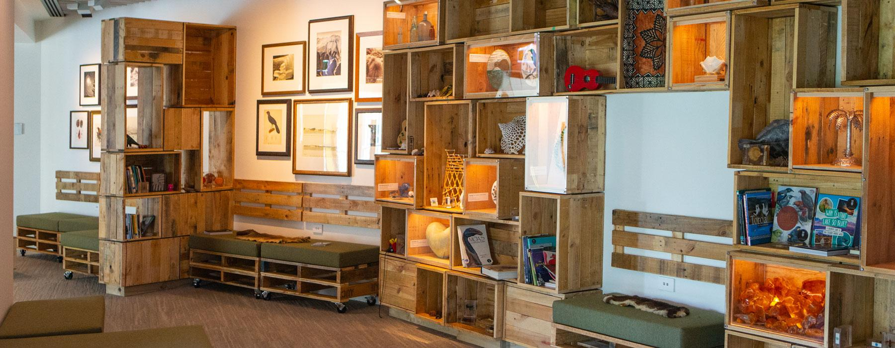 Walls covered in wooden boxes with objects inside, and lots of sofas