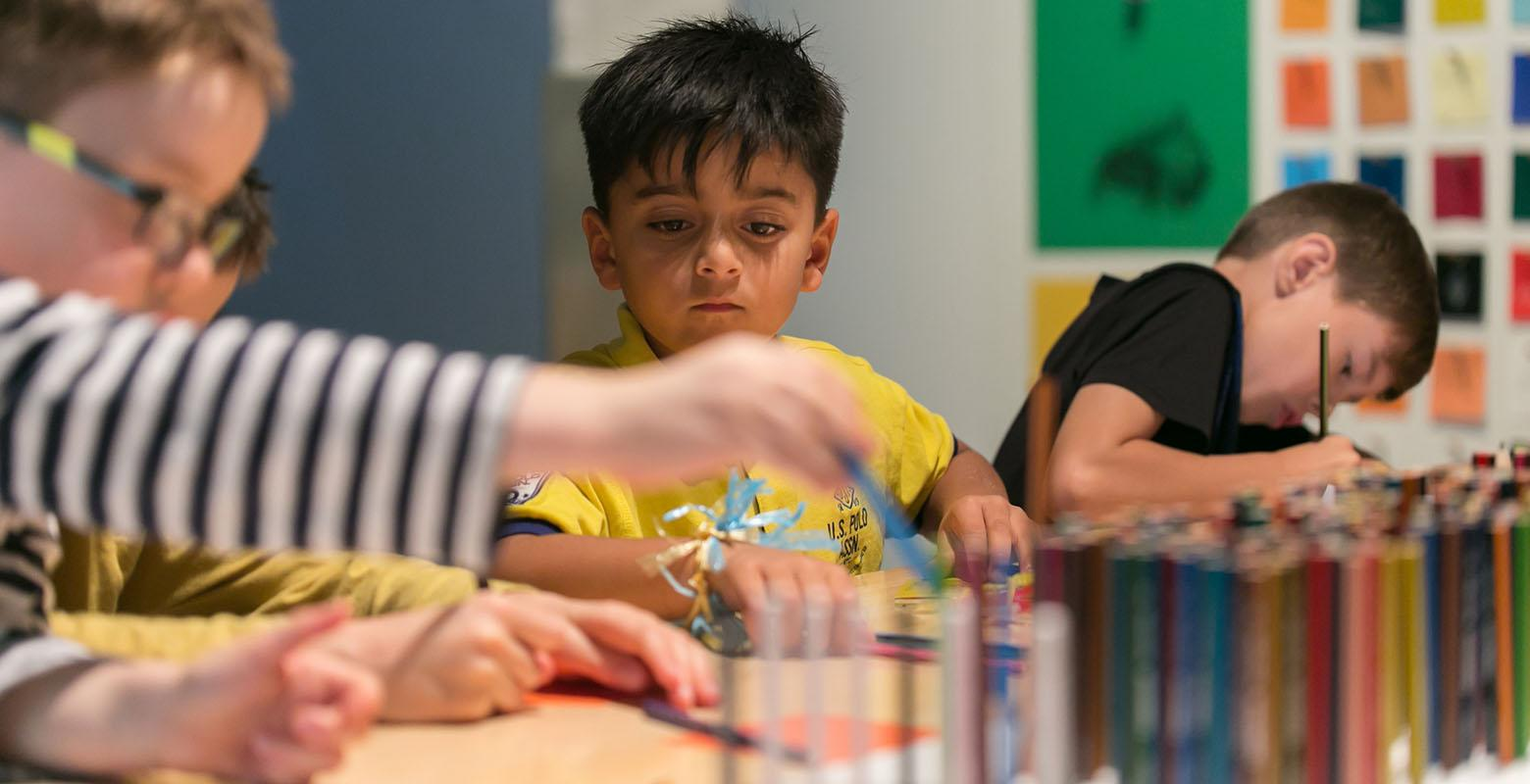 Children explore activities on offer at a table