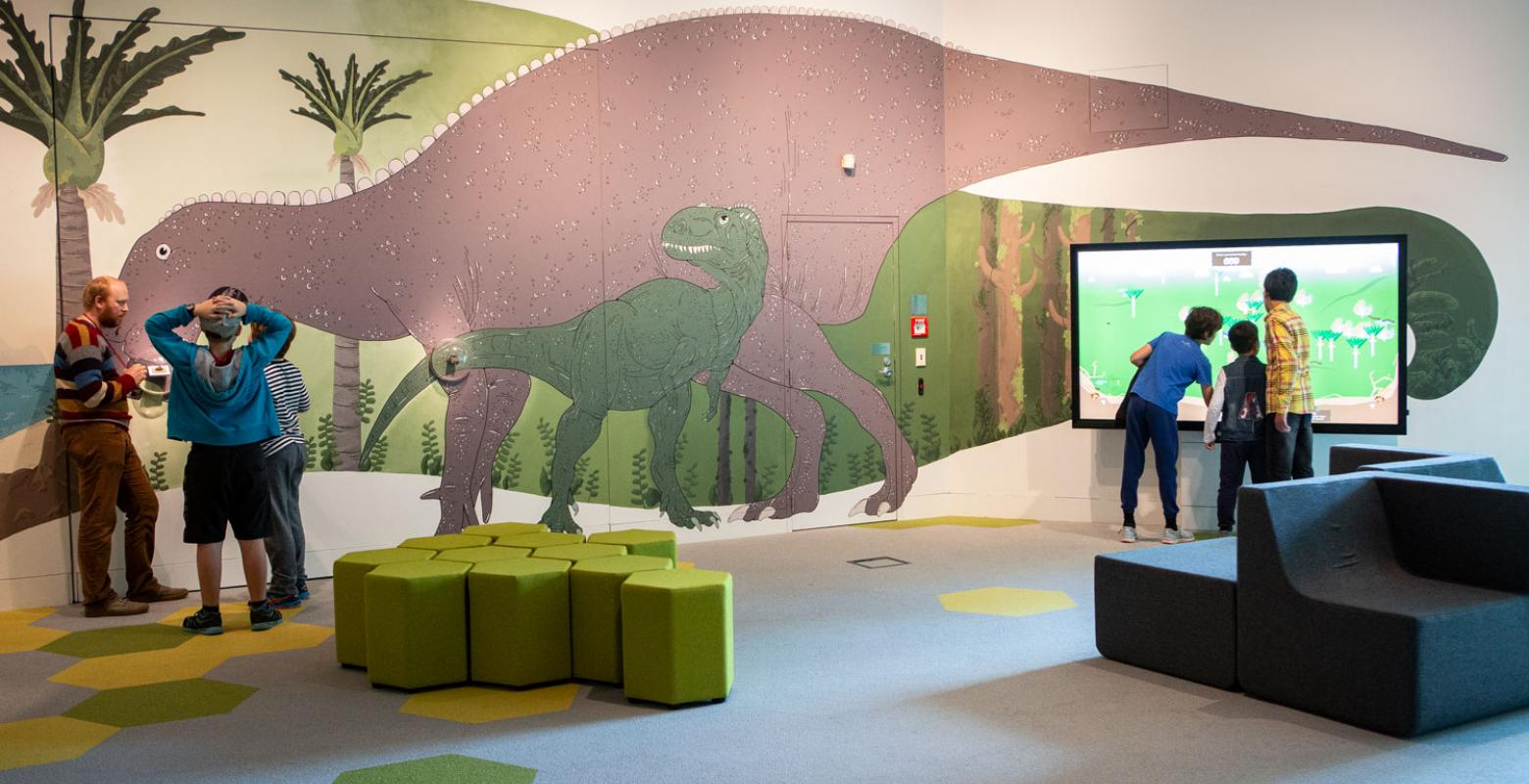 People in a room with large dinosaurs painted on the walls