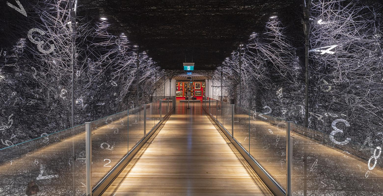 Black wool in a web stretched across a museum gallery floor, with a wooden bridge running through the middle of it. In the distance is a red wall with paintings on it.
