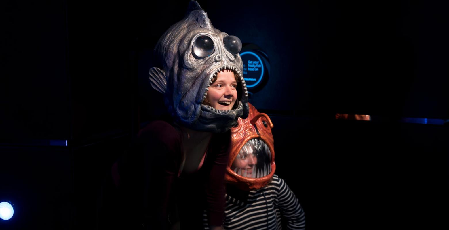 Children pose instead scary models of deep-sea fishes