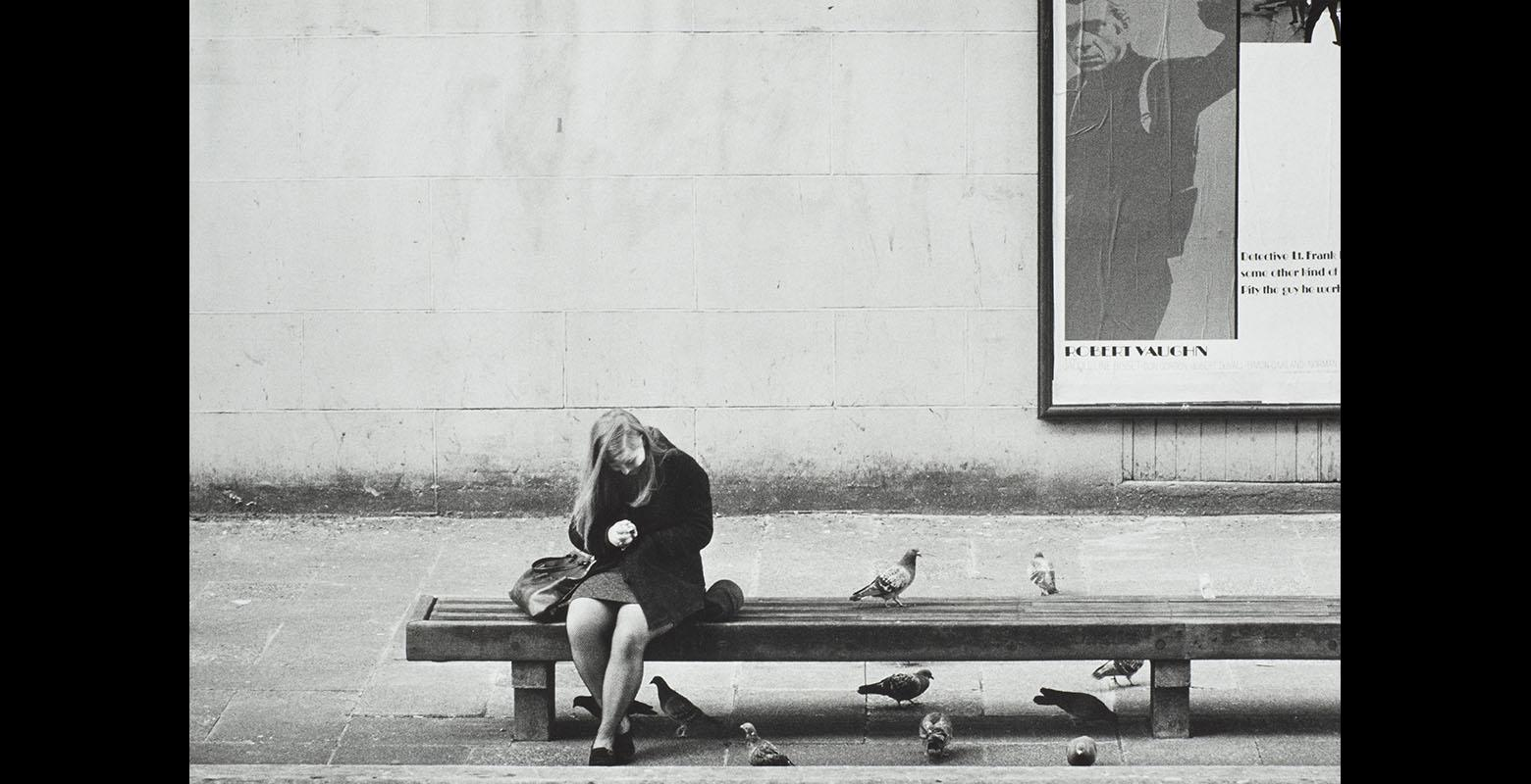 Woman sits on a bench surrounded by pigeons. Behind her on a wall is a poster for a film