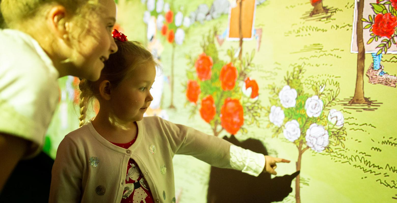 Children look at digital projections or red and white rose bushes