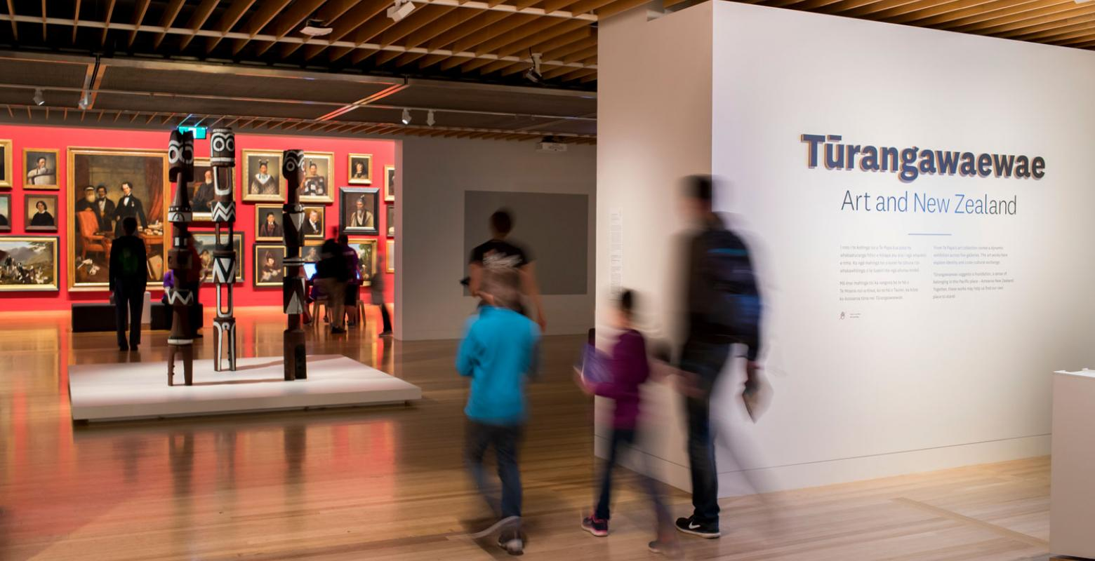 Visitors walking into the entrance of a gallery the words 'Tūrangawaewae' are on the walls
