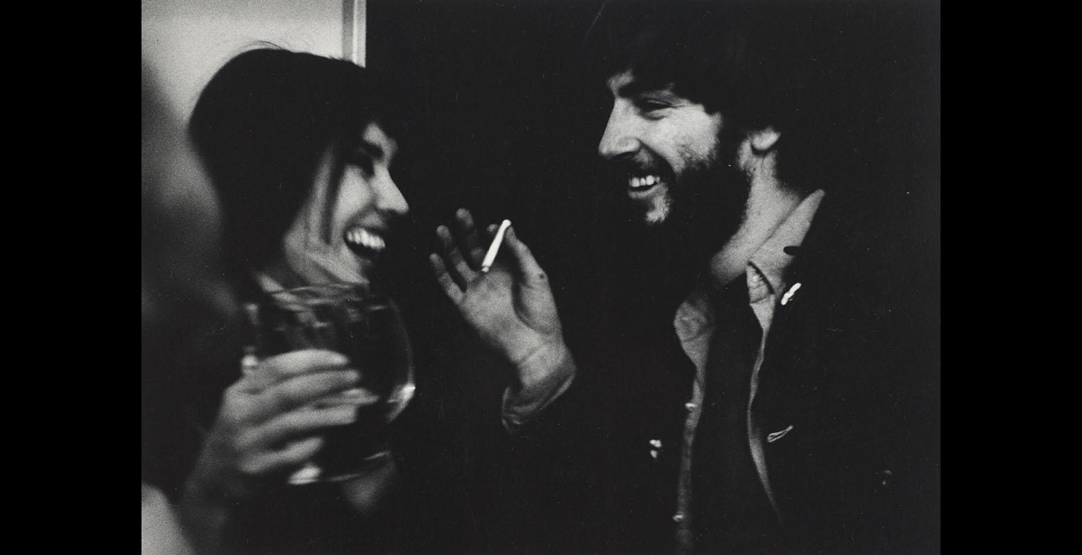 Two people laugh and smile in conversation. One is holding a glass and the other is holding a cigarette