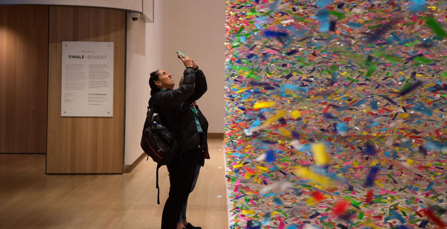 Visitor taking photos of a colourful large-scale artwork