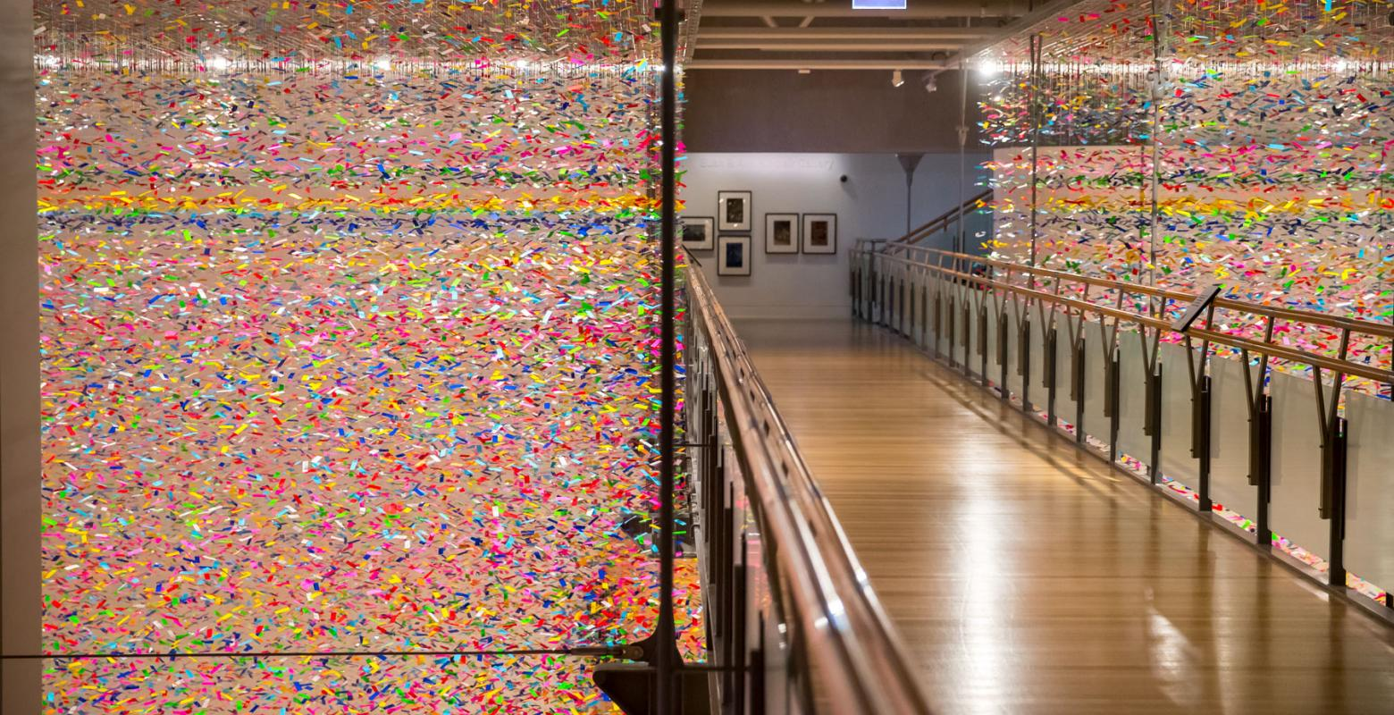 Installation shot of the colourful artwork which looks like confetti filling the whole gallery space