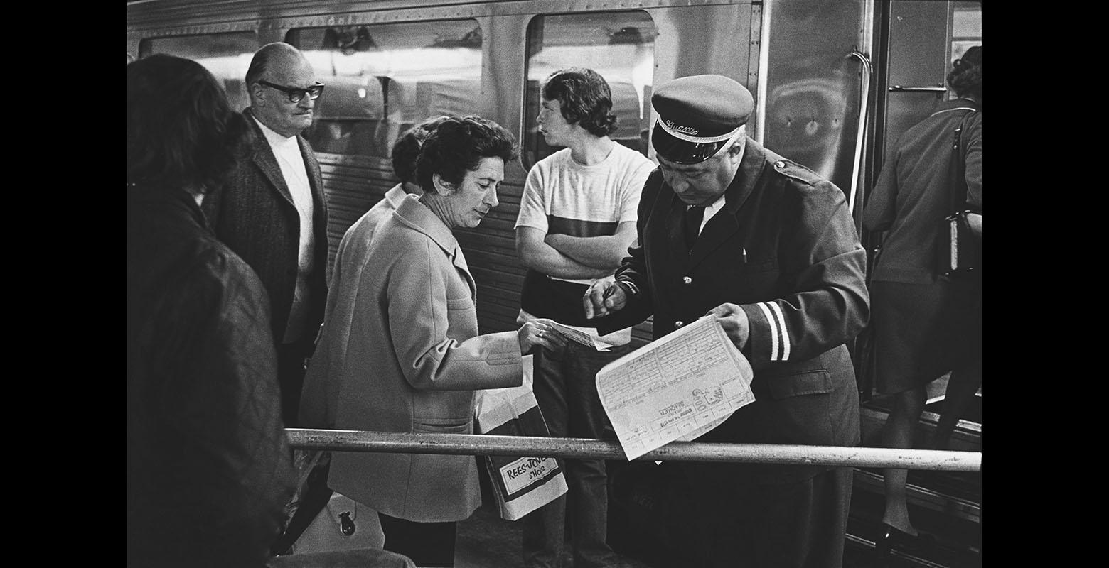 A man checks a ticket of a woman at a train station