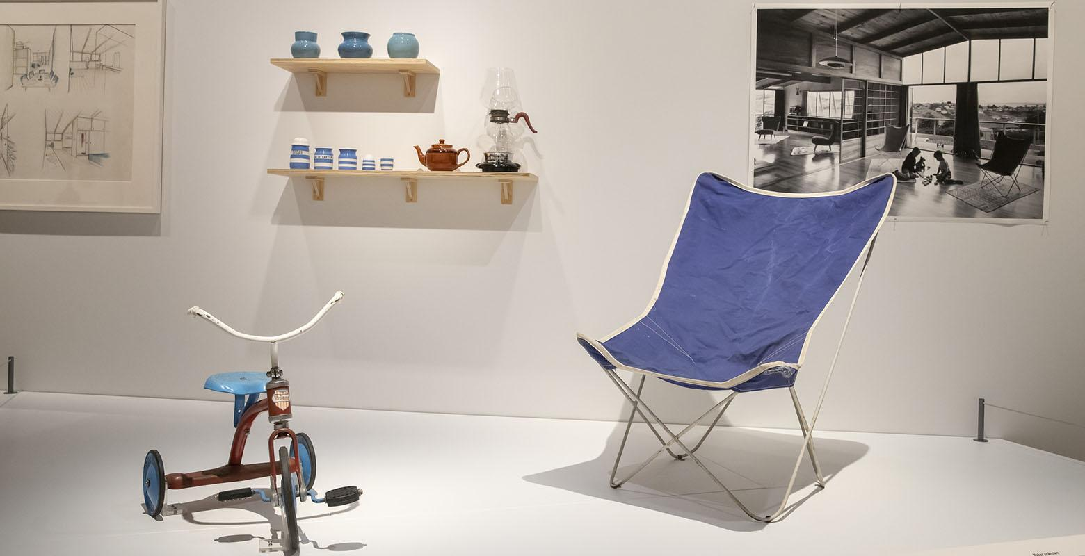 Photo of exhibition view. On a raised platform sits a red and blue trike and a blue chair. On the wall is shelving holding a coffee carafe, a tea pot, and a selection of jars. On the wall is a photo of the interior of a modernist house