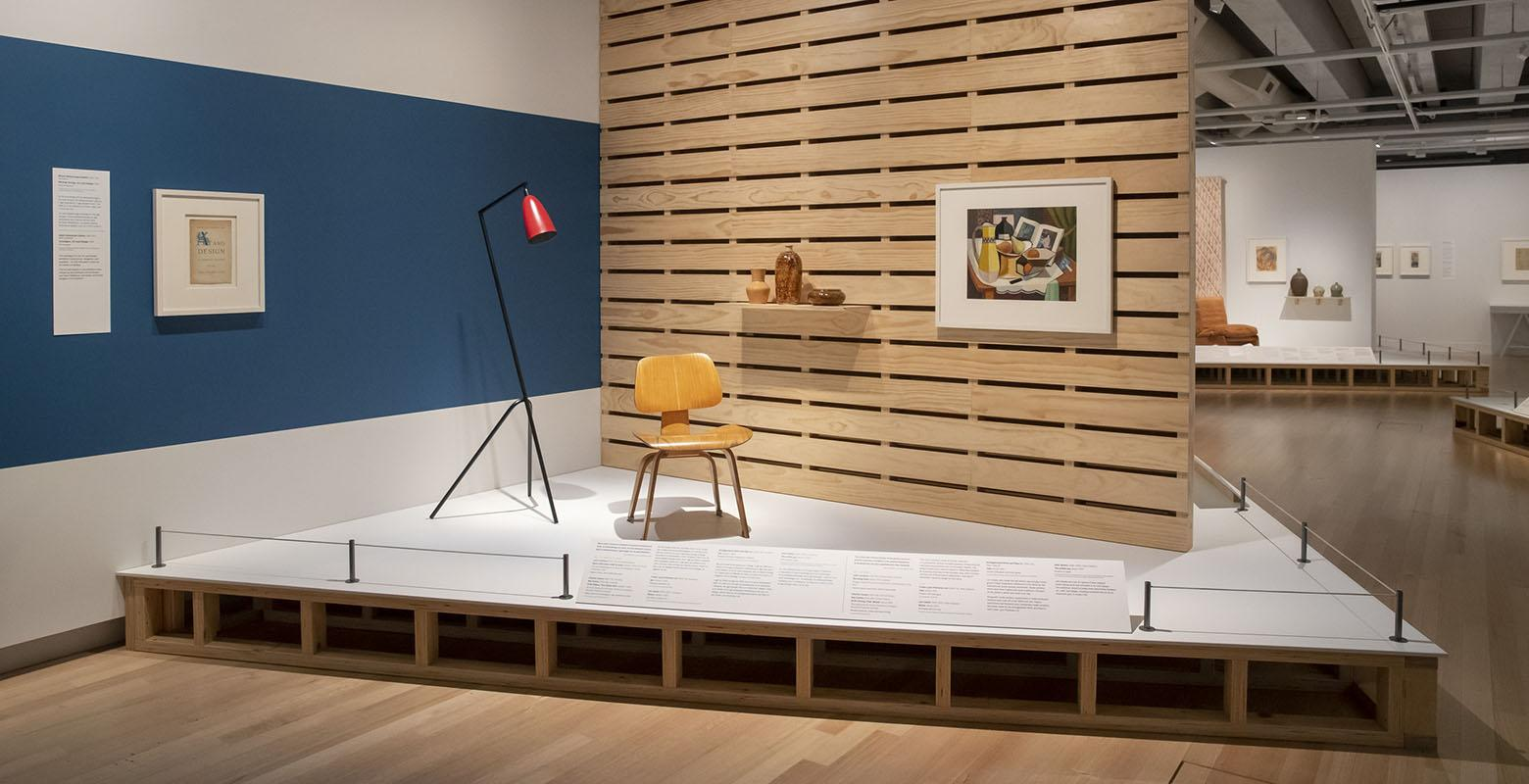 Photo of exhibition view. On a raised platform sits a chair and lamp, with a wooden wall behind. On the wall is a painting of a still life and a shelf with ceramics