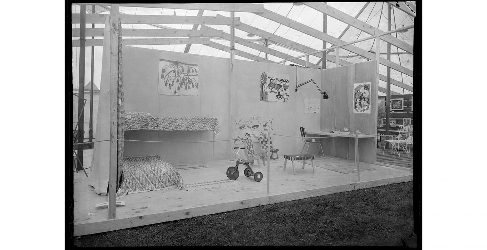 Black and white photo of a set of a room on a pallet floor in a marquee tent