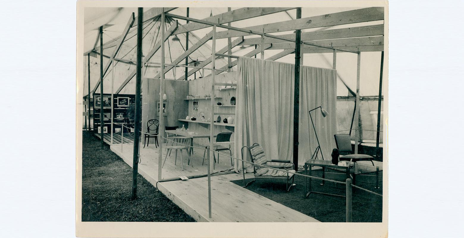 Black and white photo of a scene of a room on pallets in a marquee tent