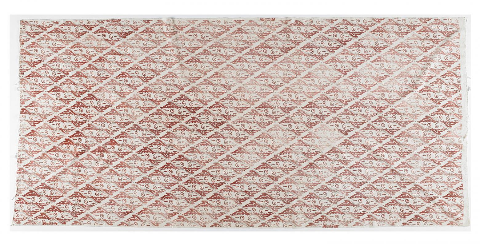 A piece of off-white material with a red pattern stamped on it