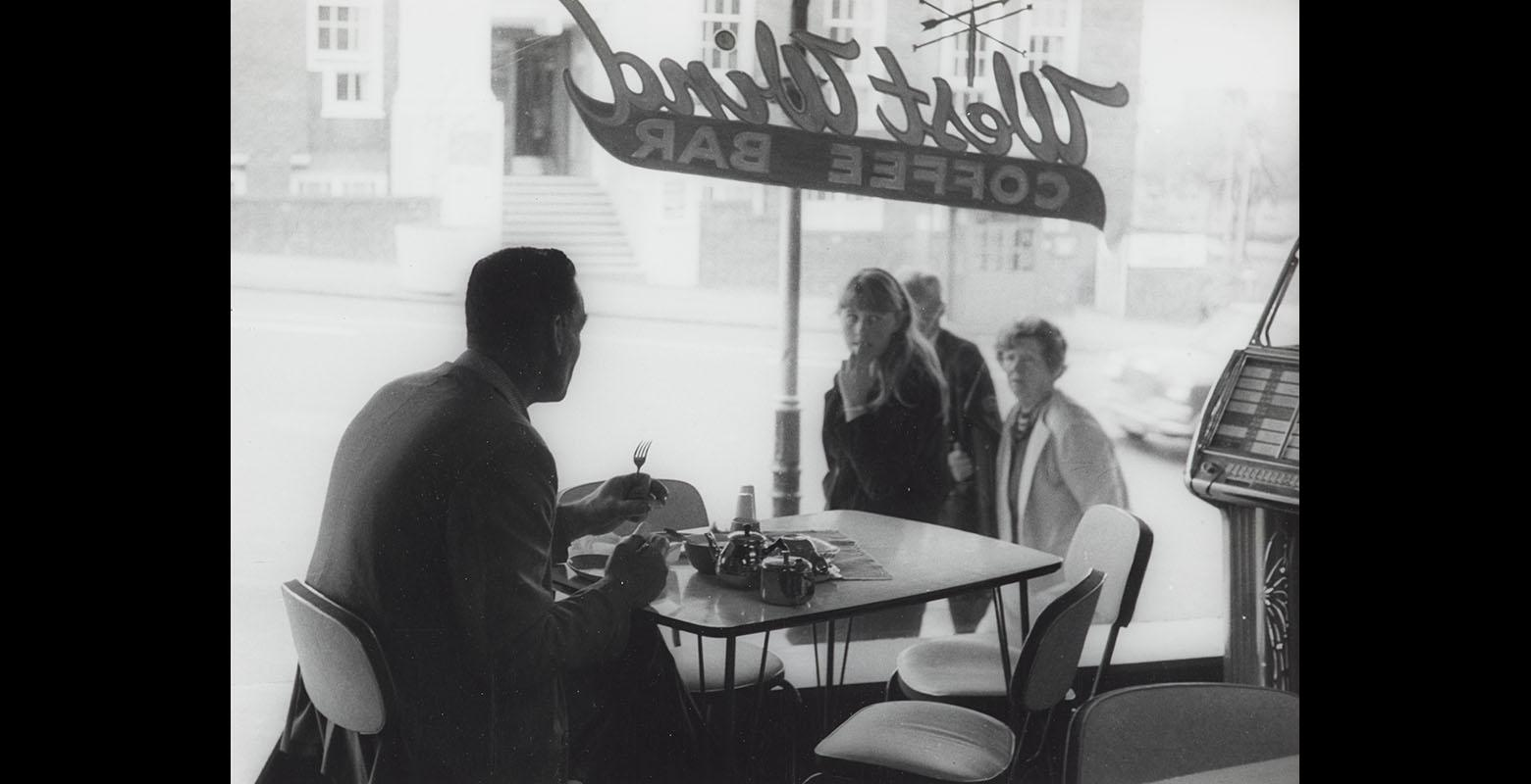 Man sits at a table alone in a cafe, looking out the window, while three people outside look in