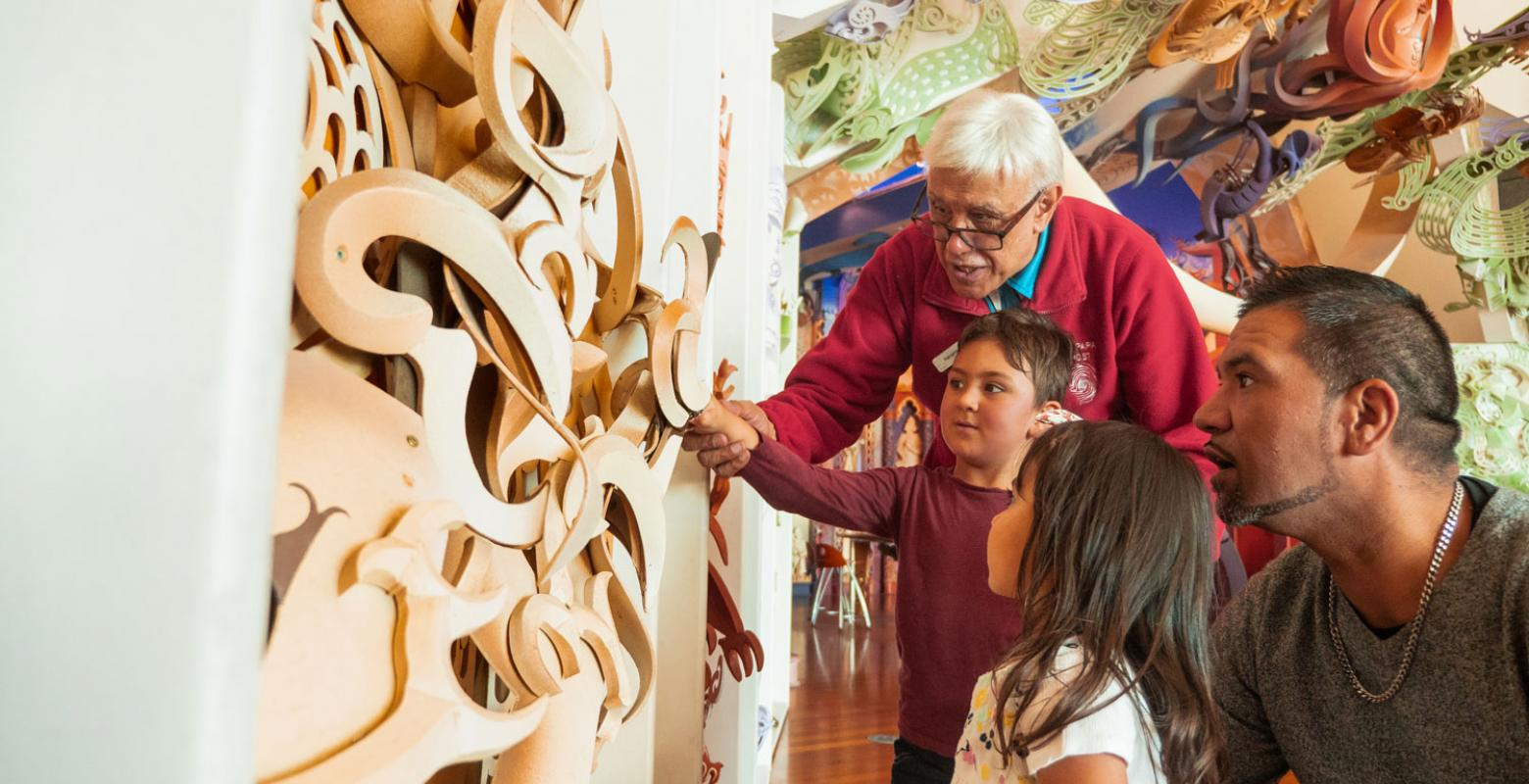 Children looking at carvings on a wharenui (large meeting house)