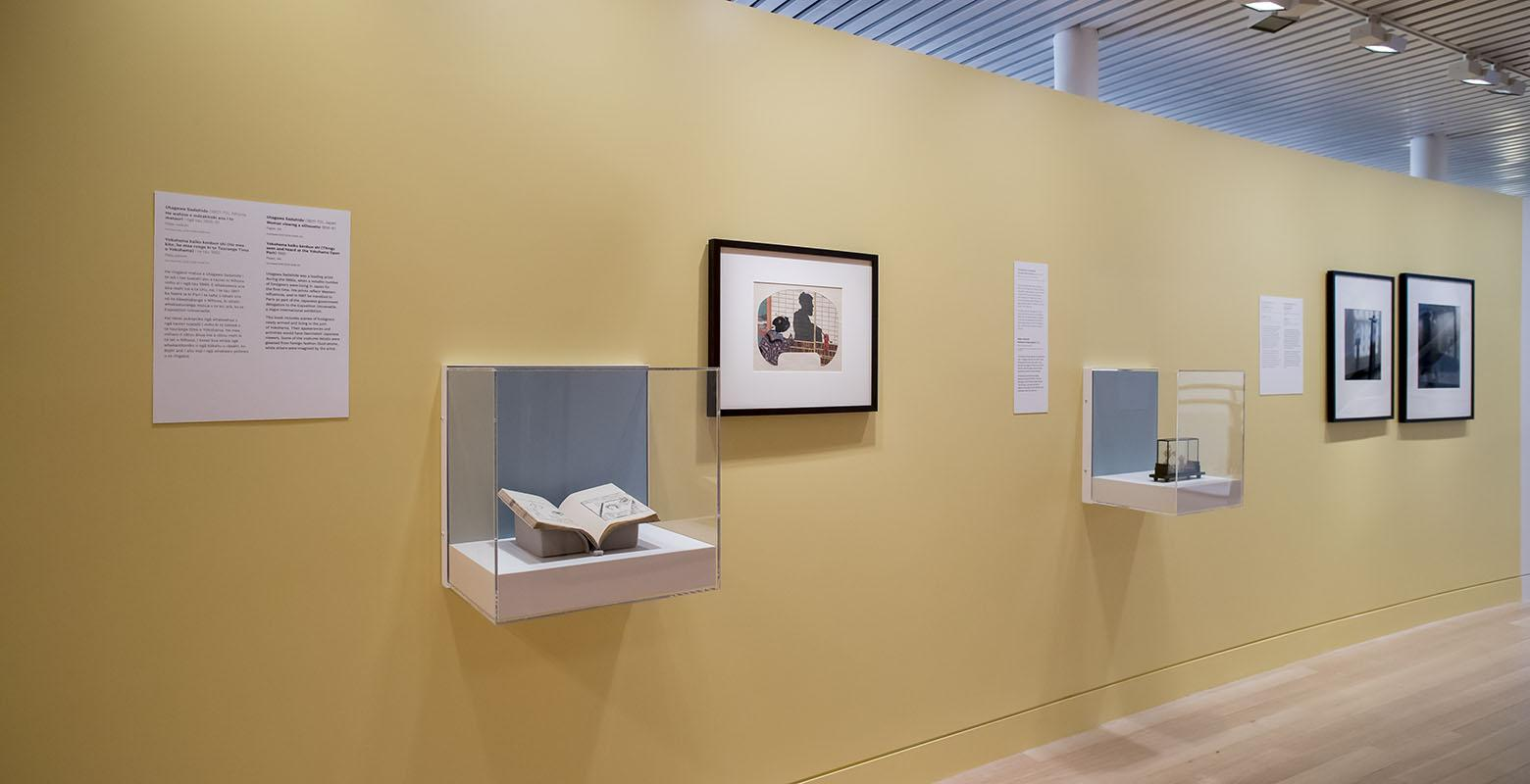 Two photographs are hung on a yellow wall, with a book and a wooden Chinese garden scene housed in display cases