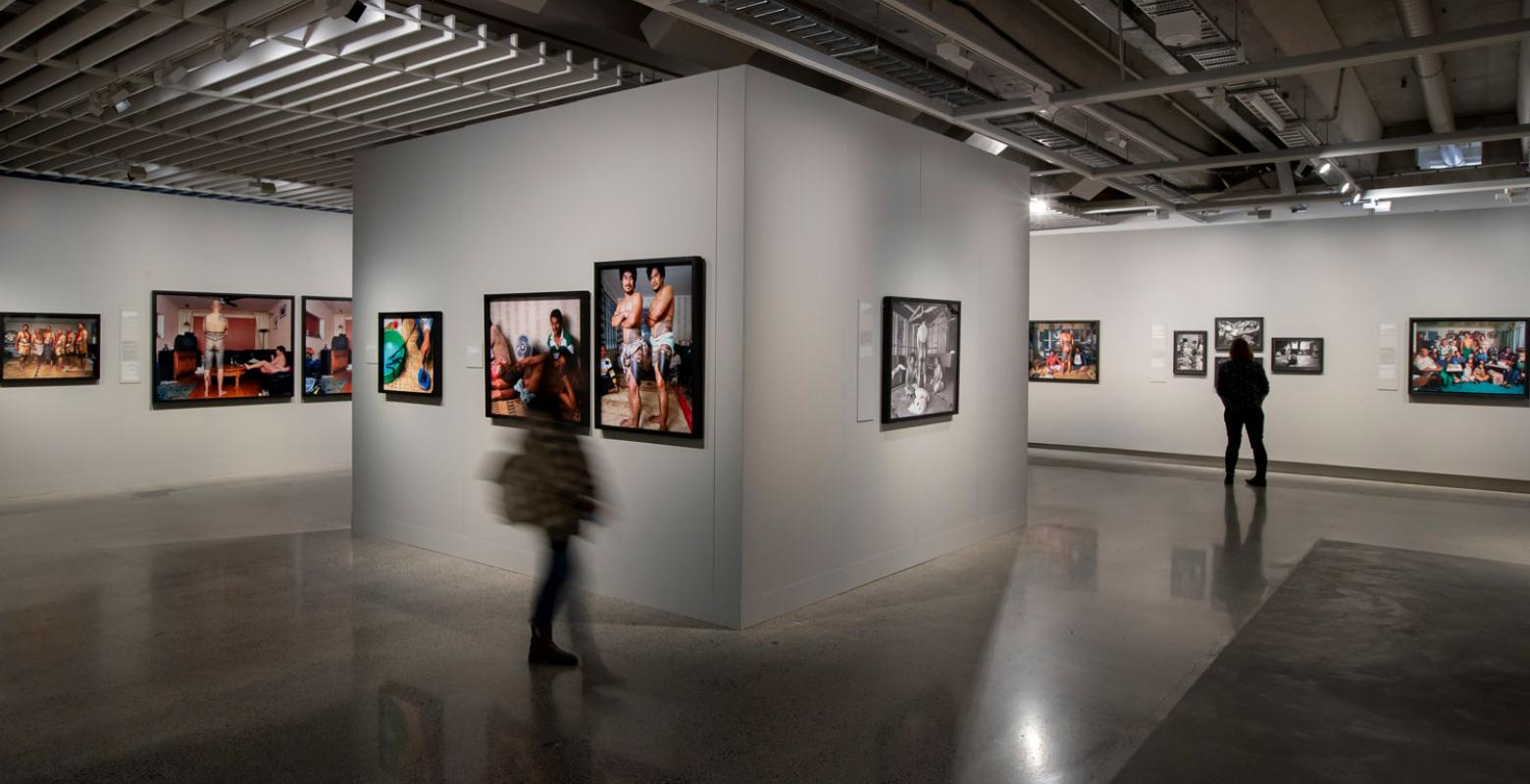 Visitors look at photos on gallery walls