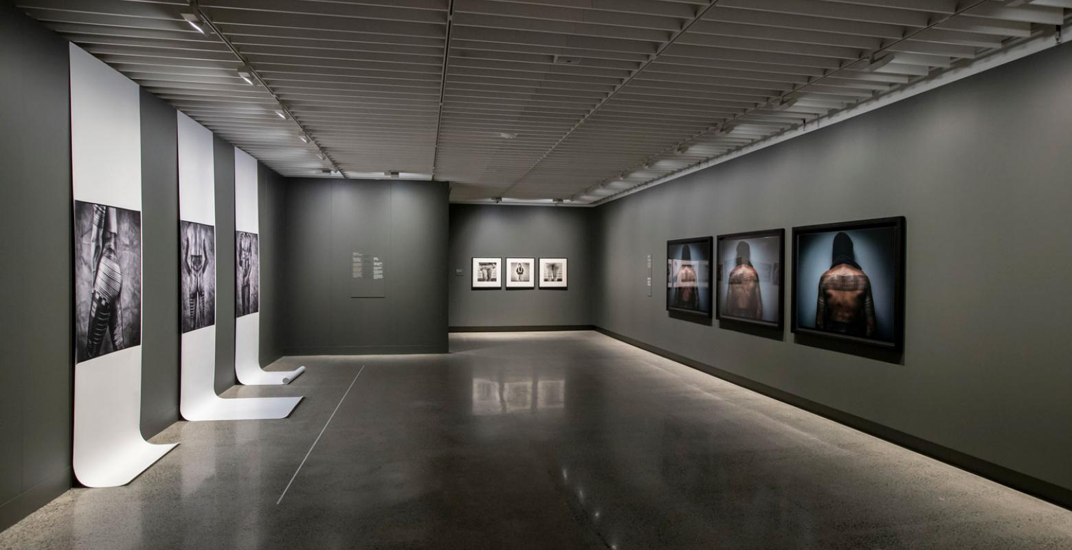 View of a gallery, photos of tattooed people on the walls