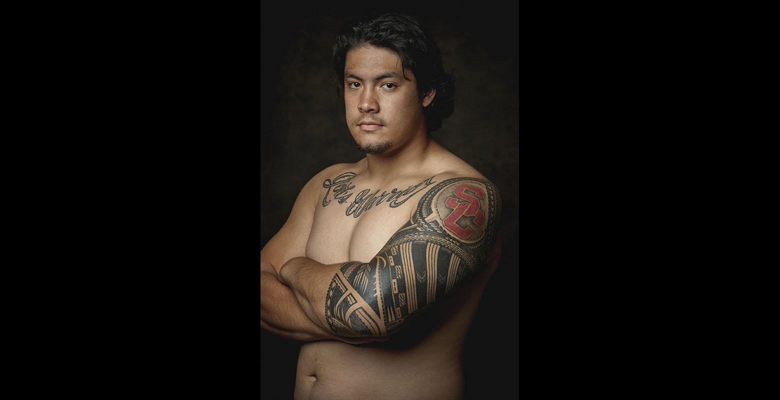 A man poses to show off his arm and chest tattoos