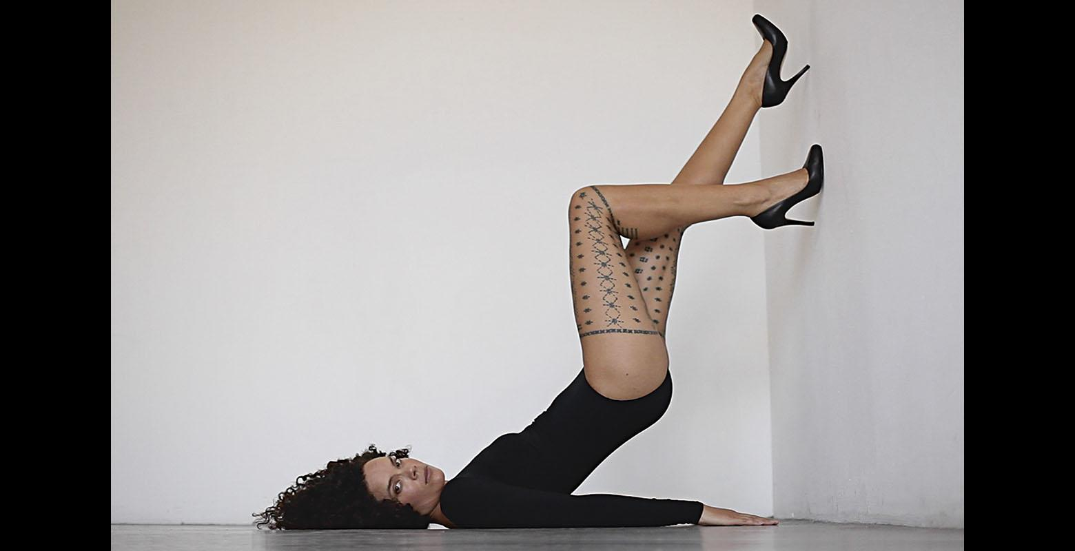 A woman lies on the floor with her legs up against a wall, revealing a detailed tattoo