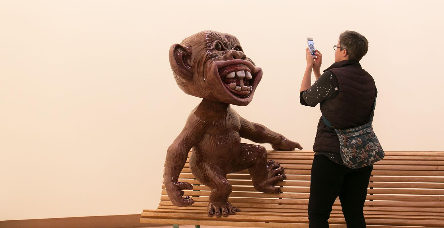 A woman takes a photo of Tiki Tour, an highly glossy sculpture of a monkey