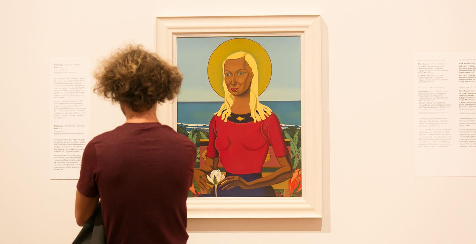 Woman looks at Rutu on the wall in Toi Art