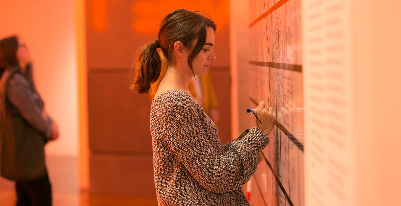 A young woman writes on a wall that resembles white bricks