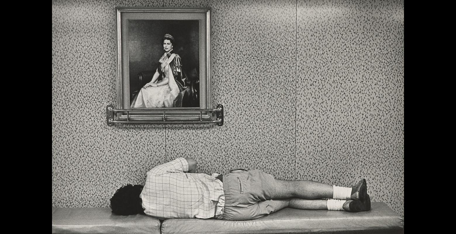 A man lies on a bench, his back to the camera. There is a portrait of Queen Elizabeth the second on the wall above him