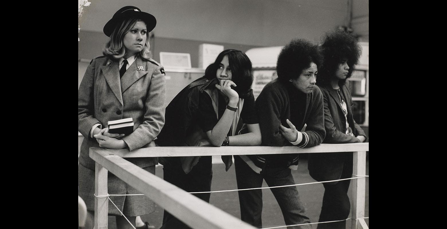 View of three young Māori men leaning on a wooden rail. On their left stands a young blonde woman in a St Johns uniform.