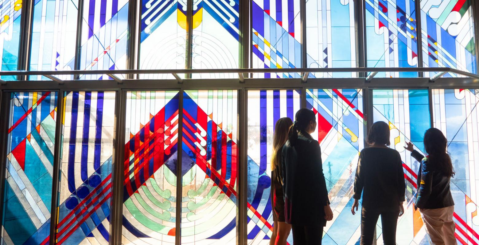 People looking at stained-glass windows