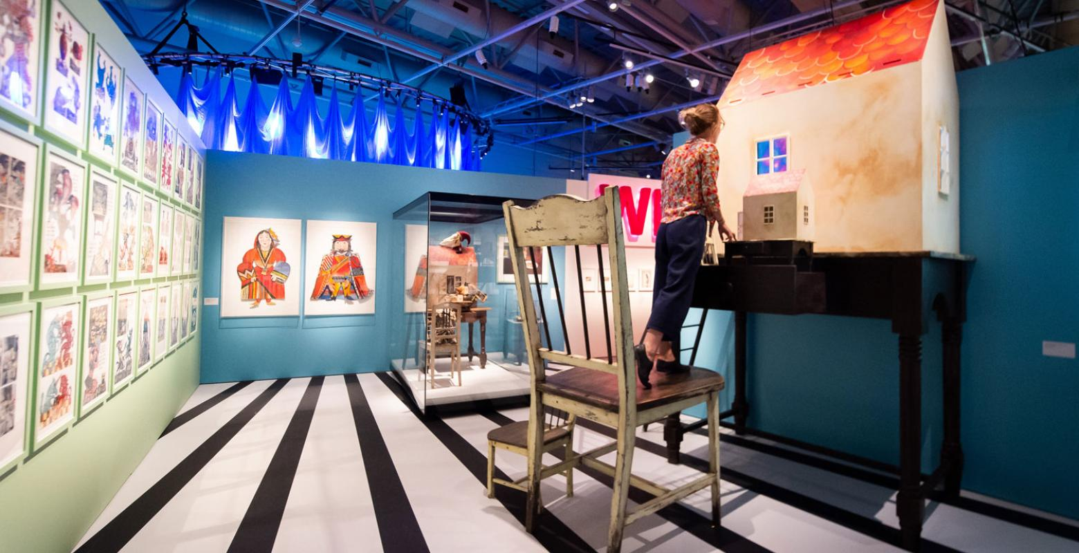 A person stand on a giant chair and peers into a dolls house