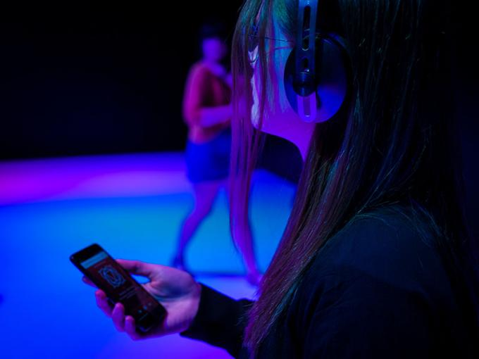Woman looks in a room filled with colour while wearing headphones