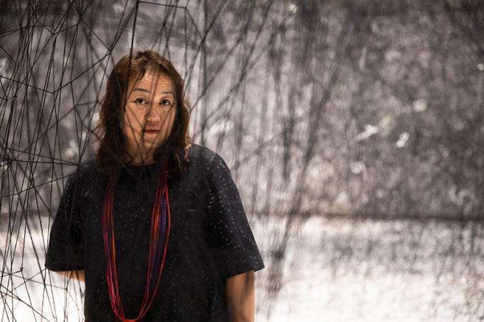 Chiharu Shiota standing among The web of time