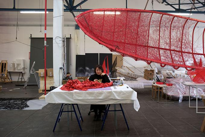 Portrait of Chiharu Shiota sitting at her desk in her studio. Above her hangs the red frame of a sailing boat frame with red wool being threaded across it