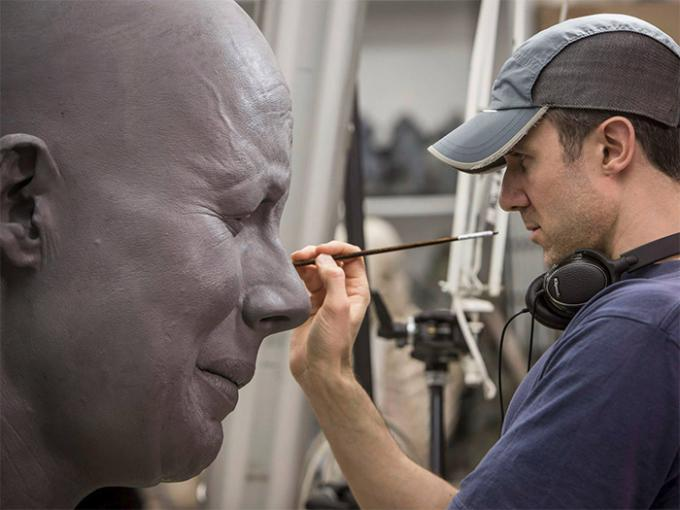 A man works on one of the giant model's faces.