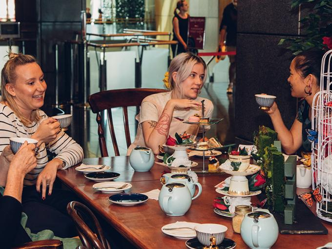 People sitting in a cafē with teapots and cups in front of them