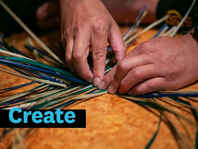 hands weaving multi-coloured strands of flax