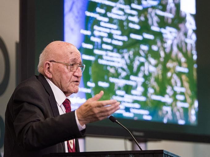 Ta Tipene addresses an audience in front of a large screen