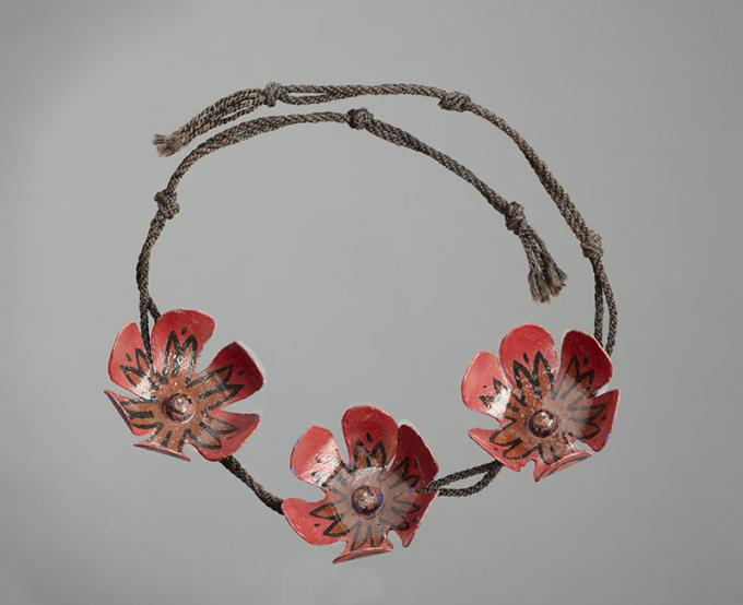 A necklace made by McCahon. It features three handcrafted red flowers on a thin woven cord