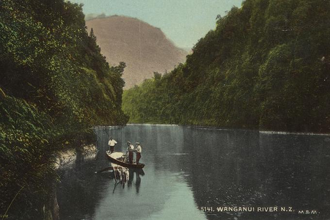 View of Whanganui River with steep sides offering a cavernous view, with three men on a kayak