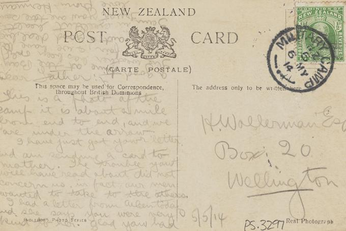 The back of a postcard containing a handwritten message in pencil