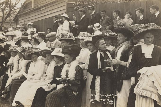 A large group of women sitting watching something out of frame. Men stand behind them